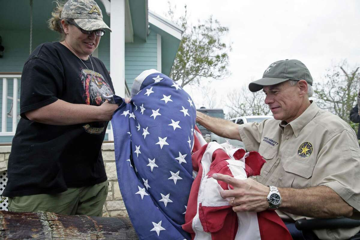 Bridget Brundrett presents a flag recovered from city hall after it had flown through Hurricane Harvey as Governor Greg Abbott visits Rockport on August 28, 2017.