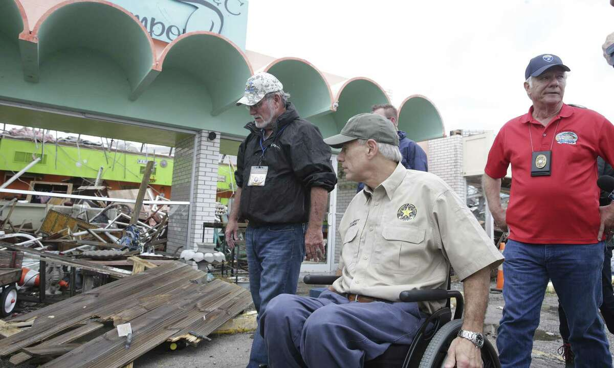 Governor Greg Abbott walks past ruin retail businesses with the mayors of Rockport and Fulton along with Senator John Cornyn as he visits Rockport on August 28, 2017.