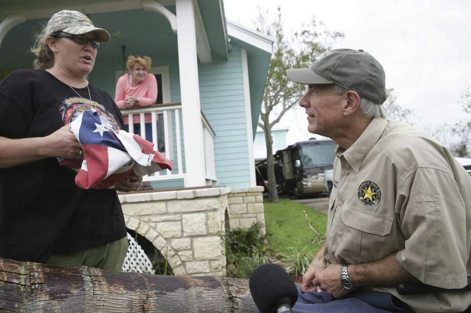 Bridget Brundrett presents a flag recovered from city hall after it had flown through Hurricane Harvey as Governor Greg Abbott visits Rockport on August 28, 2017.  In the background looking over a fallen palm tree which caught the Governor's eye is Bridget's mother Marsha Brundrett. Photo: Tom Reel, Staff / San Antonio Express-News / 2017 SAN ANTONIO EXPRESS-NEWS