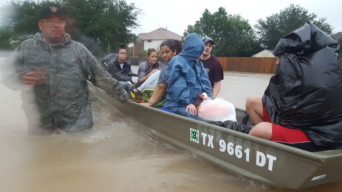 Yoel Rodriguez, 14, (in the garbage bag)& his family saw John Ochoa's boat & left home to catch it. They now wait for a national Guard truck. Yoel Rodriguez,14, said he survived a hurricane in Cuba @ age 3, but this is his first storm he remembers: