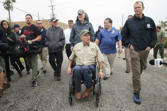 Governor Greg Abbott walks with Senator John Cornyn and FEMA representative Brock Long as he visits Rockport on August 28, 2017.