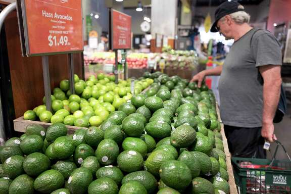 A man shops for avocados at a Whole Foods Market, Monday, Aug. 28, 2017, in New York. Amazon is moving swiftly to make big changes at Whole Foods, saying it plans to cut prices on avocados, bananas, eggs, salmon, beef and more. Amazon has completed its $13.7 billion takeover of organic grocer Whole Foods, and the e-commerce giant is wasting no time putting its stamp on the company. (AP Photo/Mark Lennihan)