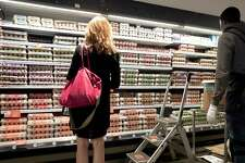 A shopper looks over the egg selection at a New York Whole Foods market. Organic eggs were among the items that cost less at Whole Foods locations as Amazon took over on Monday.