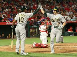 ANAHEIM, CA - AUGUST 28: Dustin Garneau #12 of the Oakland Athletics gets a high five from teammate Marcus Semien #10 after Garneau scored on his solo homerun at home plate as catcher Martin Maldonado #12 of the Los Angeles Angels of Anaheim looks on during the third inning at Angel Stadium of Anaheim on August 28, 2017 in Anaheim, California.  (Photo by Victor Decolongon/Getty Images)