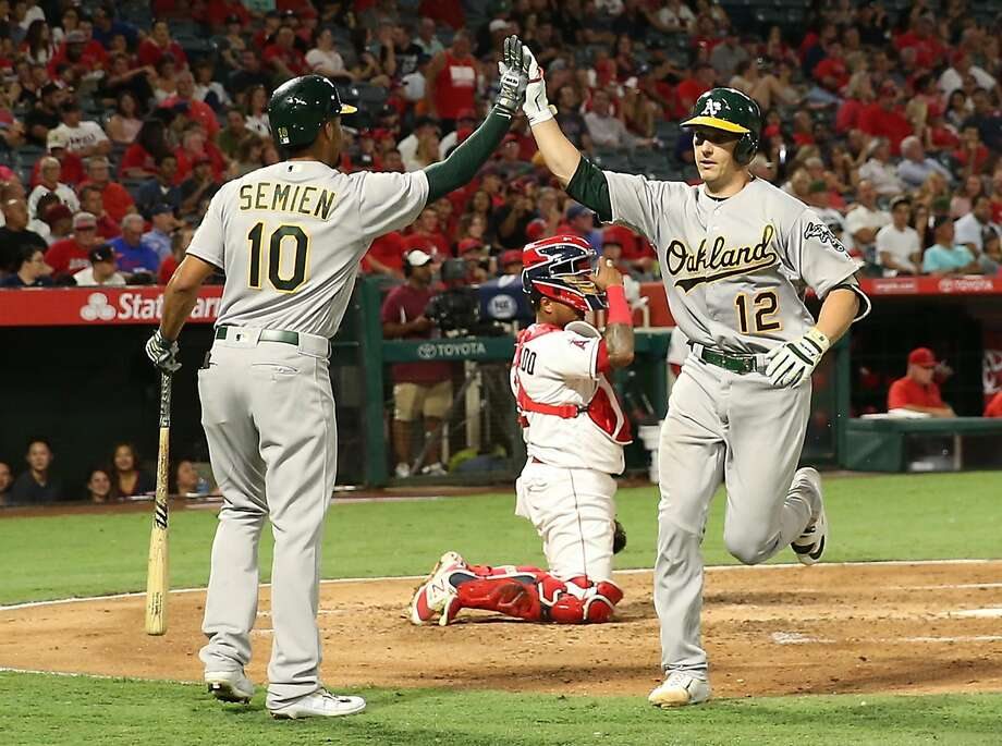 ANAHEIM, CA - AUGUST 28: Dustin Garneau #12 of the Oakland Athletics gets a high five from teammate Marcus Semien #10 after Garneau scored on his solo homerun at home plate as catcher Martin Maldonado #12 of the Los Angeles Angels of Anaheim looks on during the third inning at Angel Stadium of Anaheim on August 28, 2017 in Anaheim, California.  (Photo by Victor Decolongon/Getty Images) Photo: Victor Decolongon, Getty Images