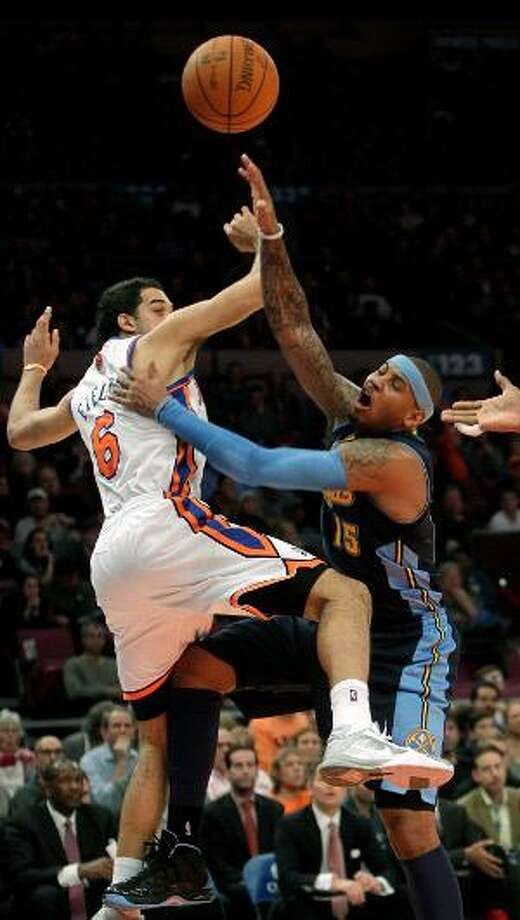 Denver Nuggets' Carmelo Anthony, right, and New York Knicks' Landry Fields fight for a rebound in the first half of Sunday's game in New York. (AP Photo/Seth Wenig)