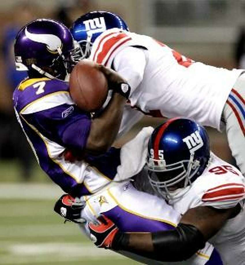 Minnesota Vikings quarterback Tarvaris Jackson (7) is tackled by New York Giants defensive tackle Rocky Bernard and safety Kenny Phillips in the the first half of their game at Ford Field in Detroit, Monday. (AP Photo/Paul Sancya)