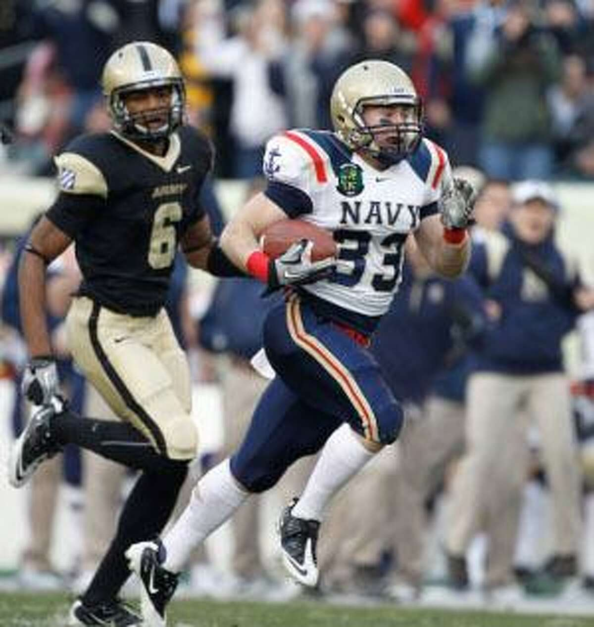 AP Navy running back John Howell, right, runs past Army cornerback Donovan Travis to score a touchdown in the first half of Saturday's game in Philadelphia. The Midshipmen won 31-17.