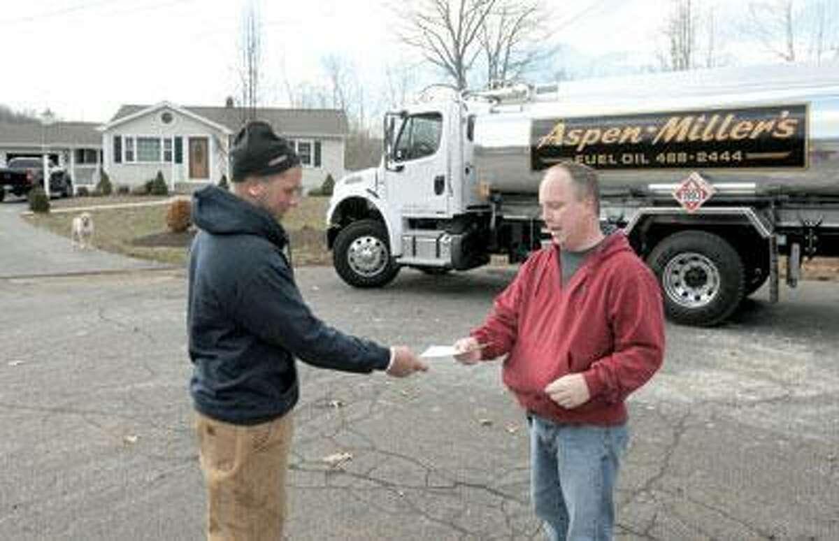 Anthony Miller, an oil delivery driver for Aspen-Miller's Fuel Oil of East Haven, left, hands an oil bill to homeowner Brian Celmer of North Branford. (Peter Hvizdak/Register)
