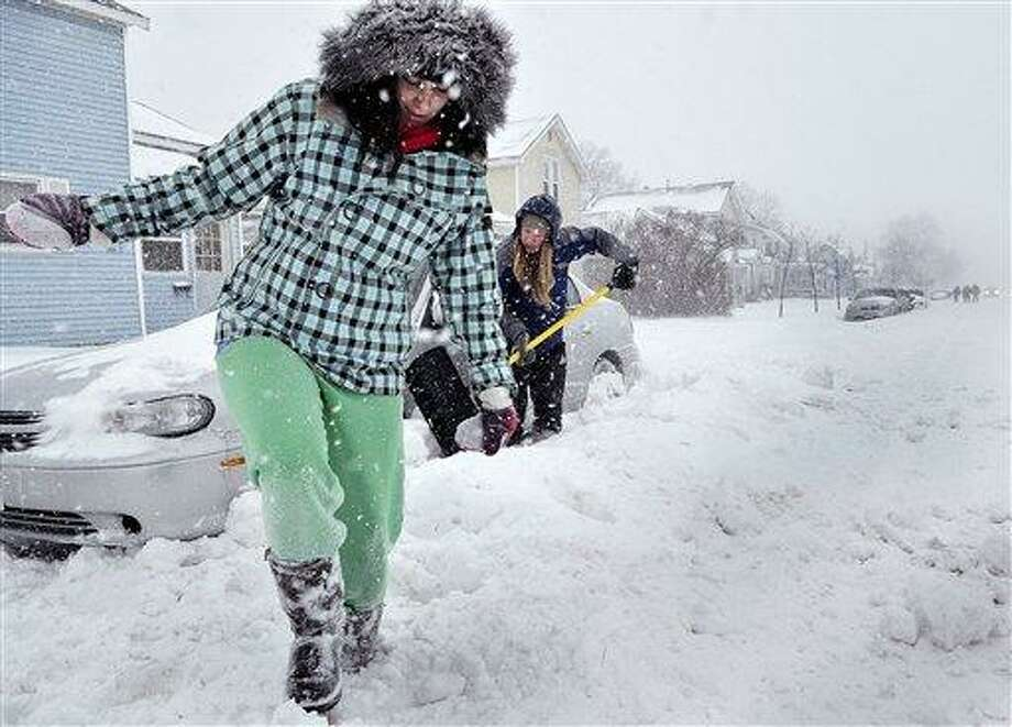UW-Eau Claire students Brook Forster, left,  and Nikki Daehne work on digging out a car parked in Eau Claire, Wis. on Saturday, Dec. 11, 2010.    The National Weather Service issued a winter storm warning, which includes Eau Claire and remains in effect until Sunday.  (AP Photo/Eau Claire Leader Telegram, Shane Opatz) Photo: AP / Eau Claire Leader Telegram