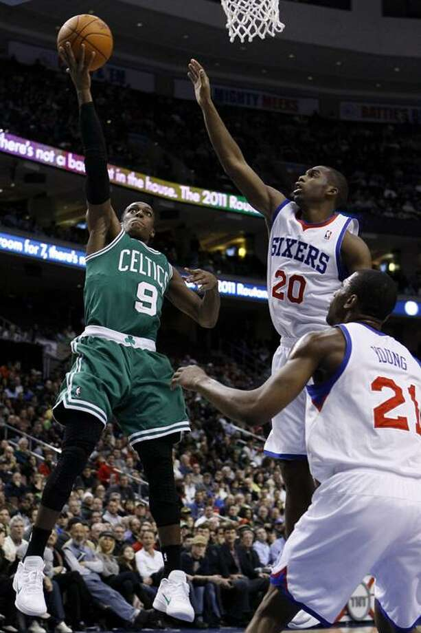 Boston Celtics' Rajon Rondo (9) goes up for a shot against Philadelphia 76ers' Jodie Meeks (20) and Thaddeus Young (21) in the first half of an NBA basketball game, Thursday, Dec. 9, 2010, in Philadelphia. (AP Photo/Matt Slocum) Photo: ASSOCIATED PRESS / AP2010