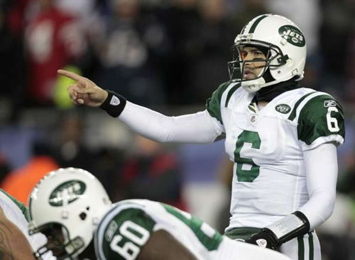 New York Jets quarterback Mark Sanchez points out a play at the line of scrimmage against the New England Patriots during the first quarter of an NFL football game, Monday, Dec. 6, 2010, in Foxborough, Mass. (AP Photo/Charles Krupa)