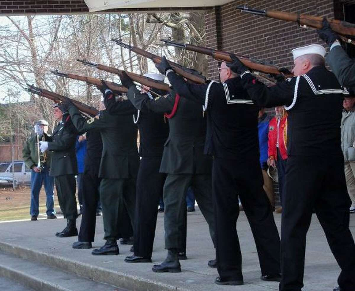 Photo by Jenny Golfin Veterans groups hosted a Pearl Harbor Day ceremony at Coe Memorial Park Tuesday. Above, members of the veterans Honor Guard fire rifles during the outdoor portion of the event.