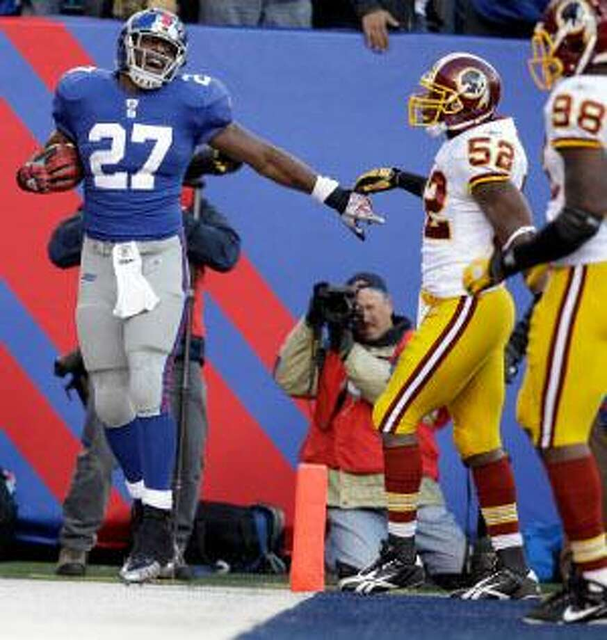AP New York Giants running back Brandon Jacobs (27) celebrates after scoring a touchdown during the third quarter of  Sunday's game as Washington Redskins linebacker Rocky McIntosh (52) and Brian Orakpo (98) look on at New Meadowlands Stadium in East Rutherford, N.J. The Giants won the game 31-7.