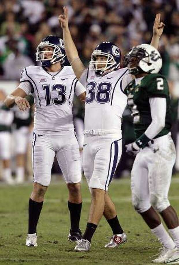 Connecticut kicker Dave Teggart (38) celebrates with holder Chad Christen (13) after kicking a 52-yard field goal with 17 seconds left to help defeat South Florida 19-16 during Saturday night's game in Tampa, Fla. South Florida cornerback Quenton Washington (2) looks on. The win gave the Huskies the Big East's automatic BCS berth. (AP Photo/Chris O'Meara)