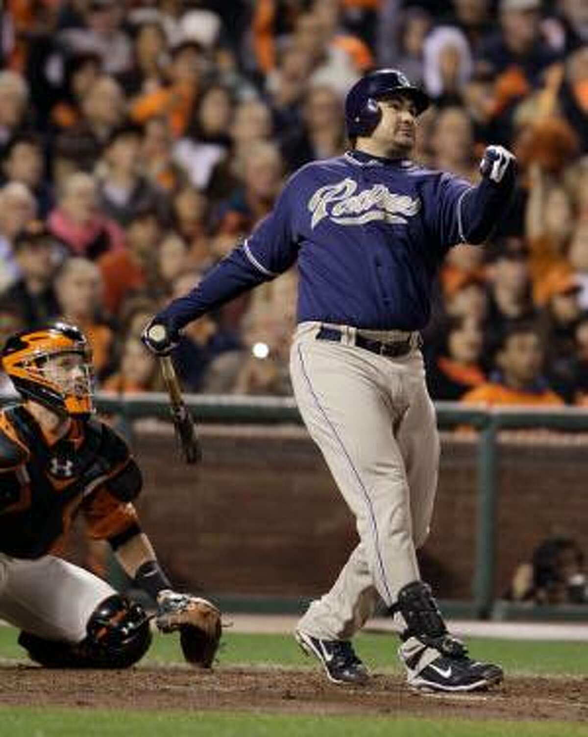 This Oct. 1, 2010, file photo shows San Diego Padres' Adrian Gonzalez hitting a three-run homer off San Francisco Giants starting pitcher Matt Cain during the third inning of their game in San Francisco. At left is San Francisco Giants catcher Buster Posey. Gonzalez has flown to Boston to take a physical exam needed to complete a trade from the San Diego Padres to the Red Sox, a person familiar with the situation told The Associated Press on Saturday. (AP Photo/Eric Risberg, FILE)