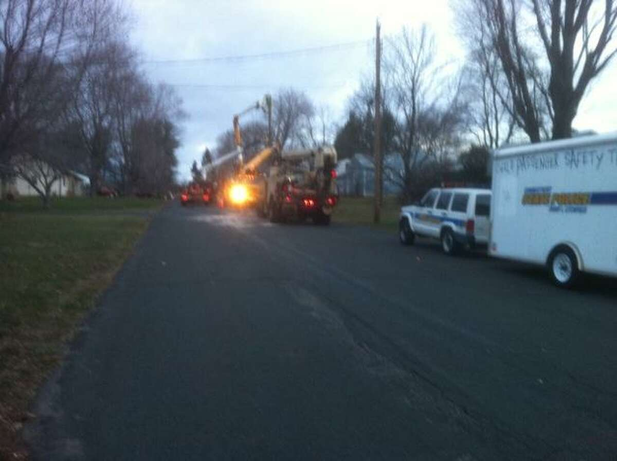 Photo by MICHAEL DRISCOLL, Special to The Register Citizen Crews from CL&P work to restore power to Pineridge Road Sunday morning after a car flipped over and took out a telephone pole.