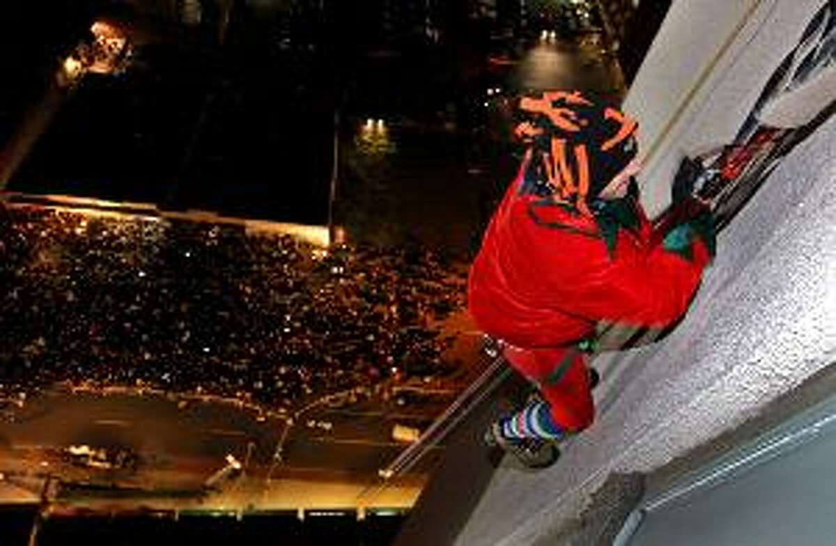 New York Yankees General Manager Brian Cashman, dressed as an elf, rappels down the face of the 22-story Landmark Building in Stamford, Conn., Sunday, as a crowd watches from below. Cashman and others rappelled down the building as part of an annual holiday celebration. (AP Photo/Craig Ruttle)