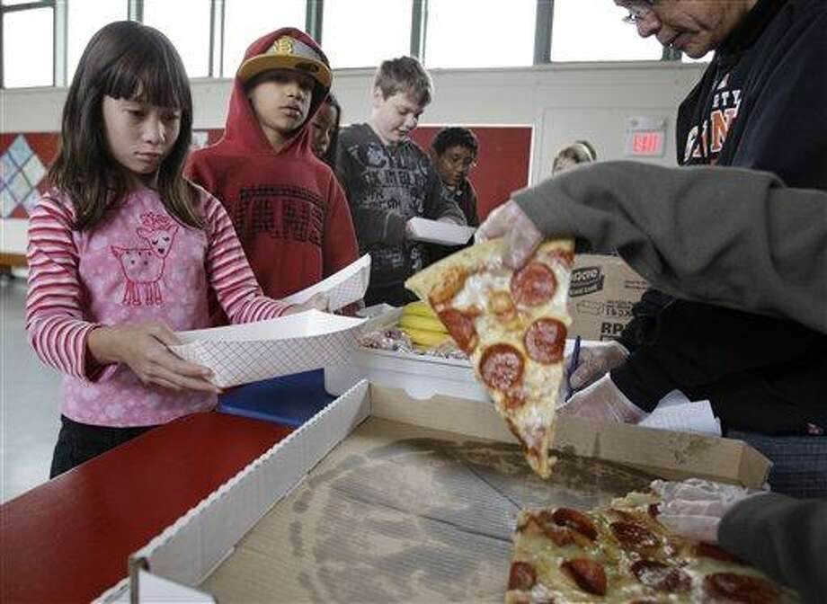 Fairmeadow Elementary School fourth grade student Juliet Lee, left, orders pepperoni pizza during a school lunch program in Palo Alto, Calif., Thursday, Dec. 2, 2010, in Palo Alto, Calif. More children would eat lunches and dinners at school under legislation passed Thursday by the House and sent to the president, part of first lady Michelle Obama's campaign to end childhood hunger and fight childhood obesity. The $4.5 billion bill approved by the House 264-157 would expand a program that provides full meals after school to all 50 states. It would also try to cut down on greasy foods and extra calories by giving the government power to decide what kinds of foods may be sold in vending machines and lunch lines. (AP Photo/Paul Sakuma) Photo: AP / AP
