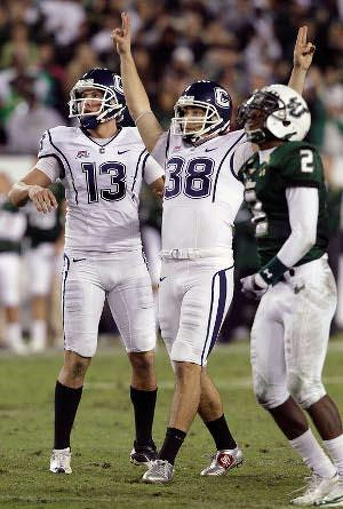 Connecticut kicker Dave Teggart (38) celebrates with holder Chad Christen (13) after kicking a 52-yard field goal with 17 seconds left to help defeat South Florida 19-16 during Saturday's game in Tampa, Fla. South Florida cornerback Quenton Washington (2) looks on. The Huskies grabbed the Big East's automatic BCS berth with the victory. (AP Photo/Chris O'Meara)
