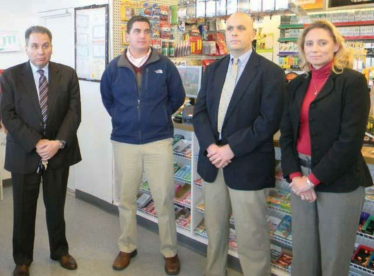 MIKE AGOGLIATI/ Register CitizenTorrington Police Chief Michael Maniago, left, stands with Mayor Ryan Bingham, Lt. Mike Emanuel and state Rep. Michelle Cook, D-65 during a press conference on Thursday. The conference was held at the Sunoco gas station and USA Food mart at 882 East Main St. where management removed the substance known as K2 from shelves.