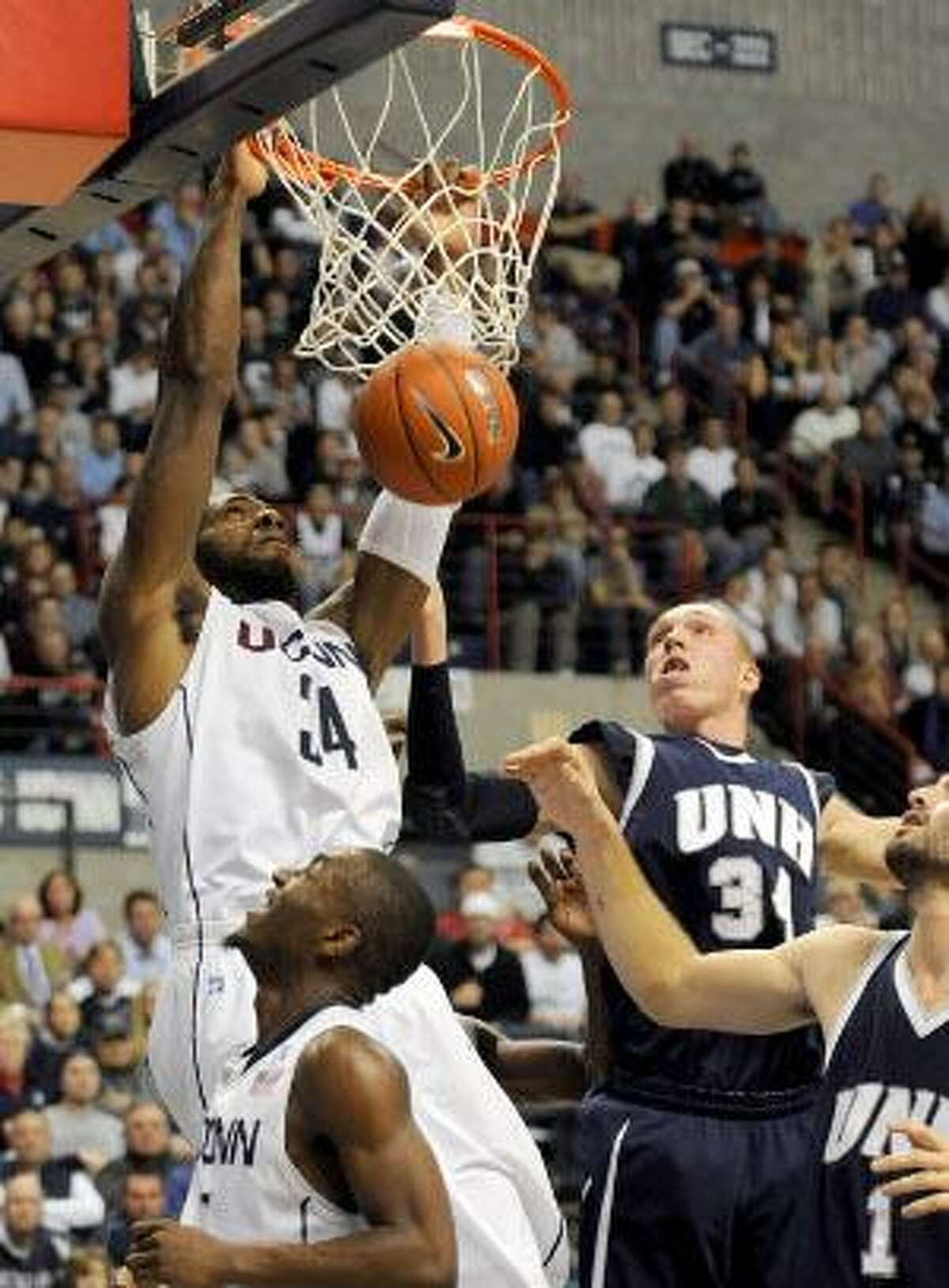 AP Connecticut's Alex Oriakhi dunks in front of New Hampshire's Brian Benson, second from right, and Dane DiLiegro, right, while Connecticut's Kemba Walker, foreground, watches in the second half of a game in Storrs, Tuesday.