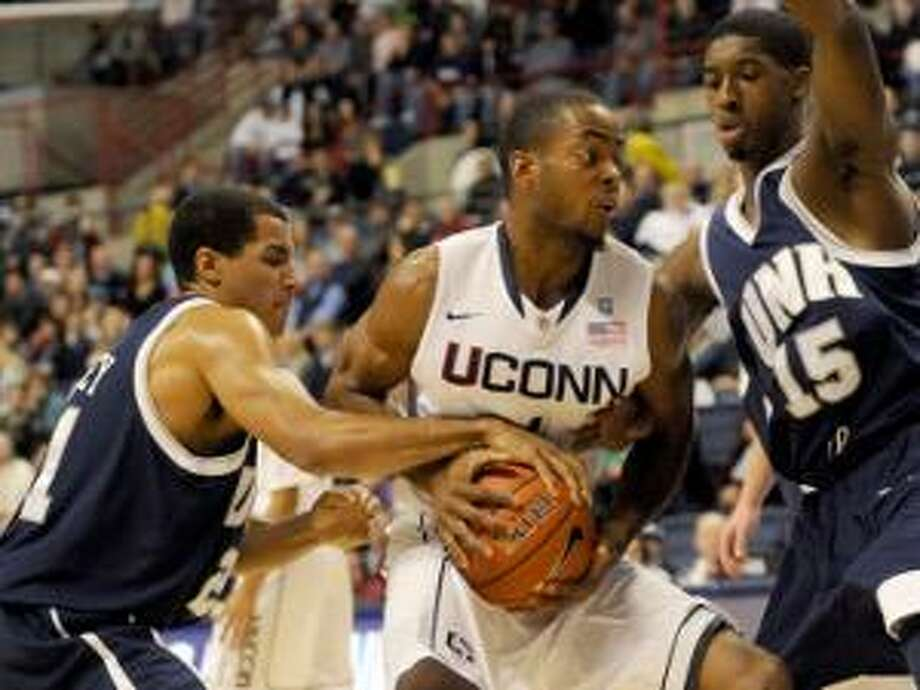 AP Connecticut's Jamal Coombs-Daniel comes in for a shot as New Hampshire's Tyrone Conley, left, and Ferg Myrick try to strip away the ball in the first half of a game in Storrs, Tuesday.