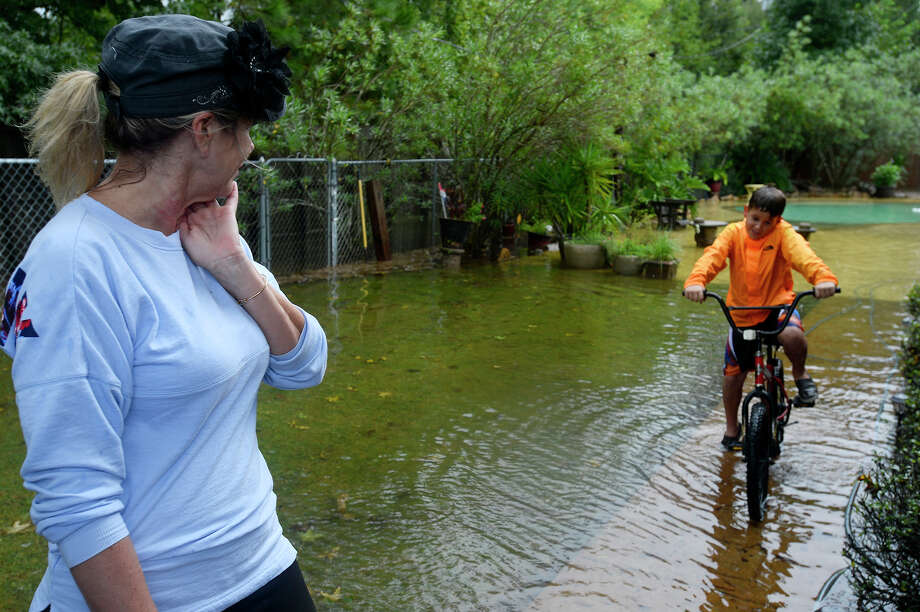 Lisa Sanders watches as her 10-year-old grandson, Branson Blanchard, rides his bike through her flooded backyard in Vidor on Monday. Rain from Tropical Storm has brought heavy rains to the region.  Photo taken Monday 8/28/17 Ryan Pelham/The Enterprise Photo: Ryan Pelham / ©2017 The Beaumont Enterprise/Ryan Pelham