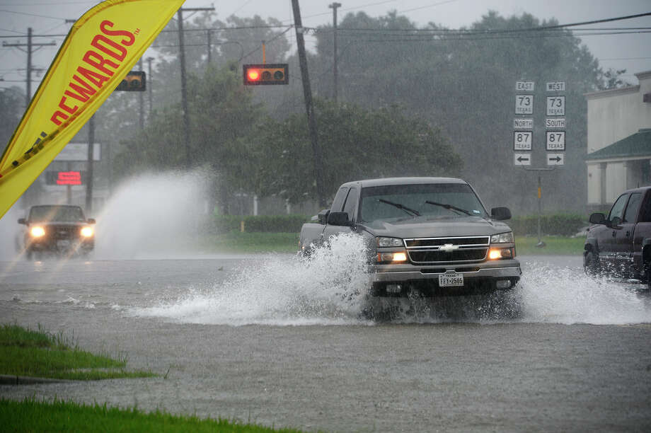 Motorists drive through flood waters at the corner of Texas 73 and Texas 87 in Bridge City on Monday. Rain from Tropical Storm has brought heavy rains to the region.  Photo taken Monday 8/28/17 Ryan Pelham/The Enterprise Photo: Ryan Pelham / ©2017 The Beaumont Enterprise/Ryan Pelham