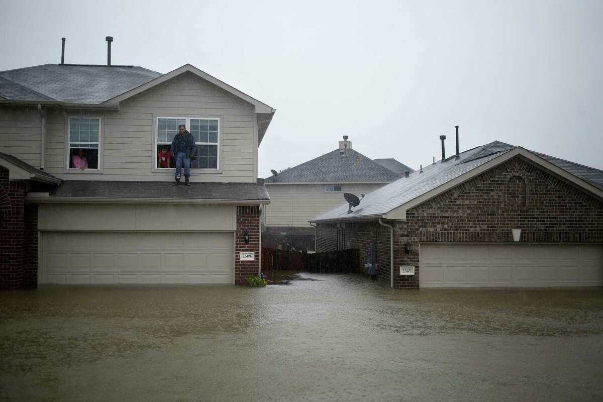 A man stands on the second story ledge of house while waiting to be rescued from rising floodwaters due to Hurricane Harvey in Spring, Texas, U.S., on Monday, Aug. 28, 2017. A deluge of rain and rising floodwaters leftHoustonimmersed and helpless,crippling a global center of the oil industry and testing the economic resiliency of a state that's home to almost 1 in 12 U.S. workers. Photographer: Luke Sharrett/Bloomberg