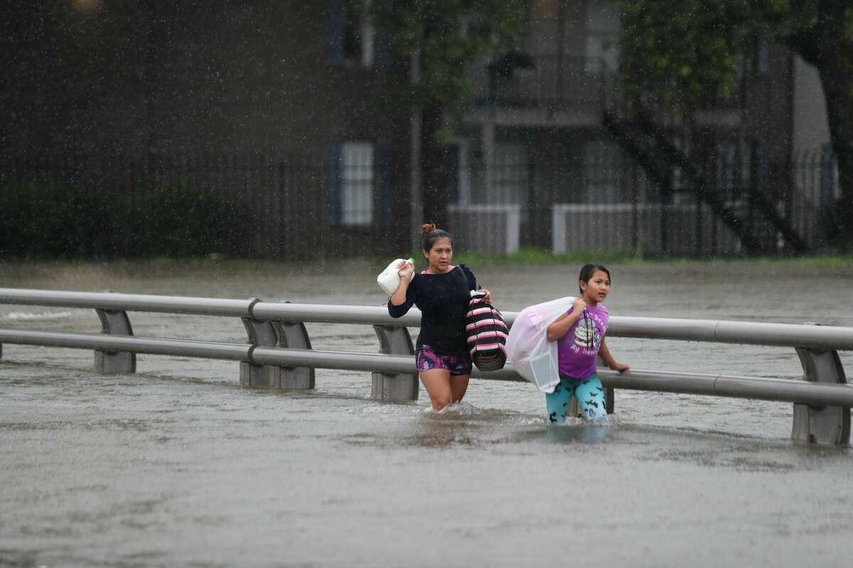 Residents from Watonga Boulevard cross the flooded White Oak Bayou, Sunday, Aug. 27, 2017, in Houston. ( Marie D. De Jesus / Houston Chronicle )