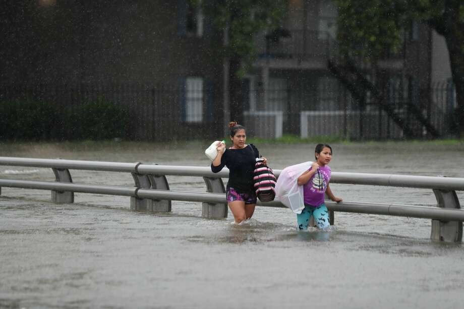 Residents from Watonga Boulevard cross the flooded White Oak Bayou, Sunday, Aug. 27, 2017, in Houston. ( Marie D. De Jesus / Houston Chronicle ) Photo: Marie D. De Jesus/Houston Chronicle