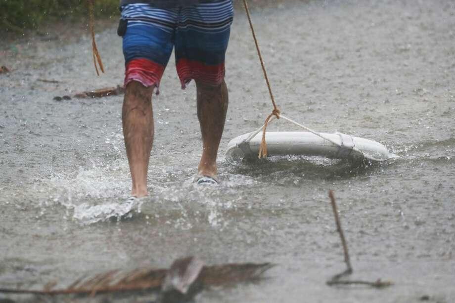 A man carried a lifesaver through flooded water near White Oak Bayou, Sunday, Aug. 27, 2017, in Houston. ( Marie D. De Jesus / Houston Chronicle ) Photo: Marie D. De Jesus/Houston Chronicle