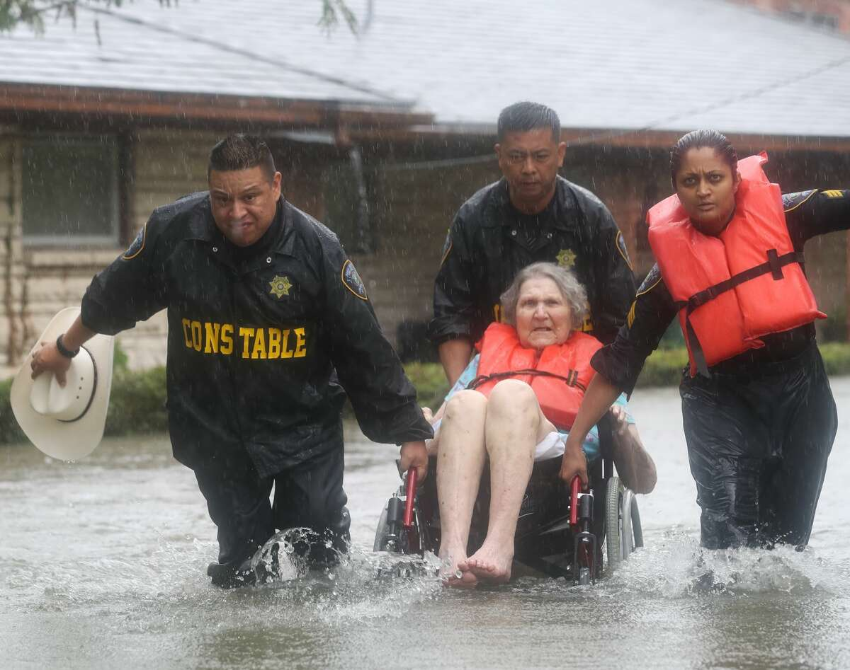 Precinct 6 Deputy Constables Sgt. Paul Fernandez, from left, Sgt. Michael Tran and Sgt. Radha Patel rescue an elderly woman from rising water on North MacGregor Way, near Brays Bayou, after heavy rains from the remnants of Hurricane Harvey, Saturday, August 27, 2017, in Houston. ( Jon Shapley / Houston Chronicle )