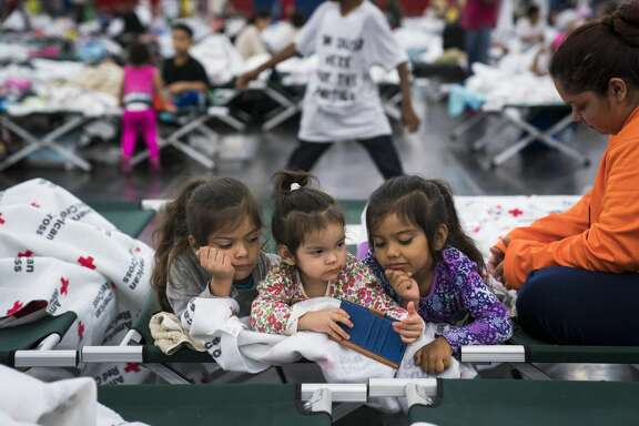 Angelina De Los Santos, 7, left, Vanessa Pasillas, 2, center, and Jade de los santos, 5, center right, watch videos with Rosemarie Pasillas, right, as people seek shelter at the George R. Brown Convention Center in Houston, TX on Monday, Aug 28, 2017. Rising water from Hurricane now Tropical Storm Harvey pushed thousands of people to rooftops or higher ground Sunday as the had to flee their homes in Houston.