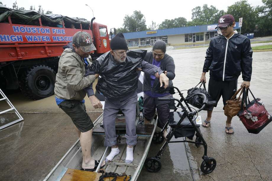 Leonel Marroquin, left, lifts his father, Heliodro Marroquin, with help from Maria Varrientos as his son, Fabian, 17, right,  waits with bags as they took their boat to a rescue point along Edgebrook  Sunday, August 27, 2017. Flooding is wide spread after rain from Hurrican Harvey. ( Melissa Phillip / Houston Chronicle) Photo: Melissa Phillip, Houston Chronicle