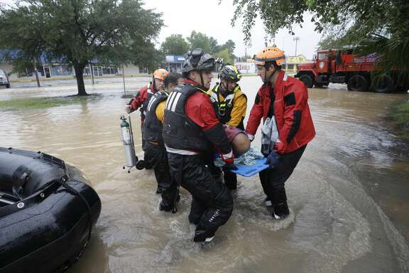 Rescuers transfer Claude Young on a back board from a boat to a pickup point along Edgebrook Sunday, August 27, 2017. The elderly man had many medical issues from a stroke in May. Flooding is wide spread after rain from Hurricane Harvey. ( Melissa Phillip / Houston Chronicle)