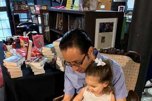 Leonardo Duenas-Osorio and his daughter, Daphne Duenas, read together Monday afternoon at Murder By The Book. The store, barely damaged by flooding, is open for anyone who needs coffee, electricity or company.