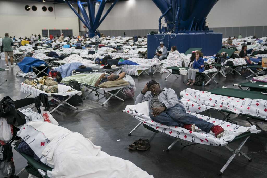 A man sleeps as people seek shelter at the George R. Brown Convention Center in