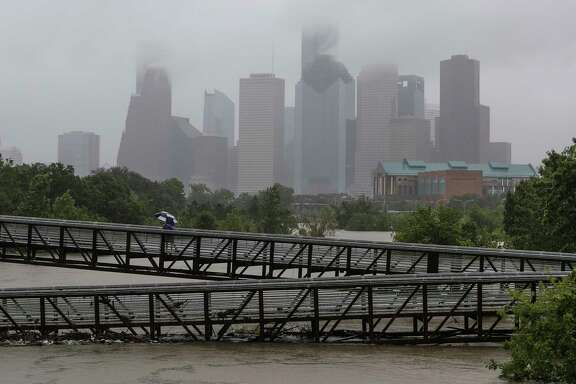 People walk over the Rosemont Pedestrian Bridge to look at a flooded Buffalo Bayou as Tropical Storm Harvey continues to dump rain over downtown Houston Tuesday, Aug. 29, 2017.