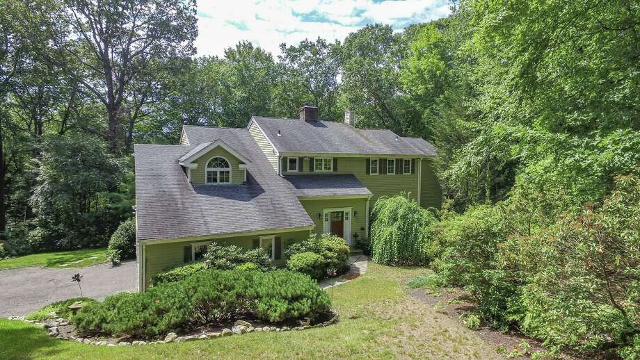 The colonial contemporary house at 28 Old Kingdom Road sits on a 2.26-acre property in a wooded setting not far from the centers of Wilton and New Canaan.