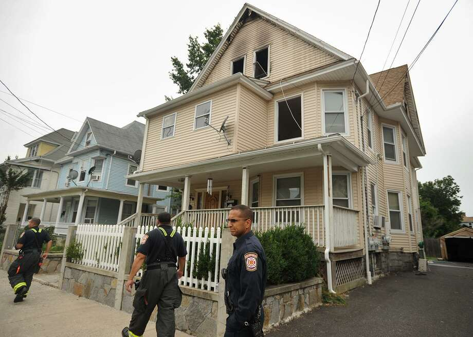 Bridgeport firefighters check on the scene of an overnight house fire at 158-160 Beechwood Avenue in Bridgeport, Conn. on Tuesday, August 29, 2017. The fire which occurred in the third floor unit of the occupied three family home, was reportedly connected to a domestic dispute. The owner-occupied first floor and vacant second floor apartments suffered water damage. Photo: Brian A. Pounds / Hearst Connecticut Media / Connecticut Post