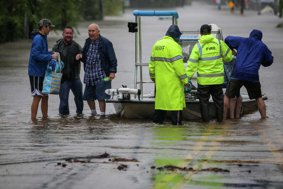 Emergency responders and Good Samaritans escort residents out of the flooded community on Pruitt Road in Spring on Monday, Aug. 28, 2017. (Michael Minasi / Chronicle) Photo: Michael Minasi, Staff Photographer / © 2017 Houston Chronicle