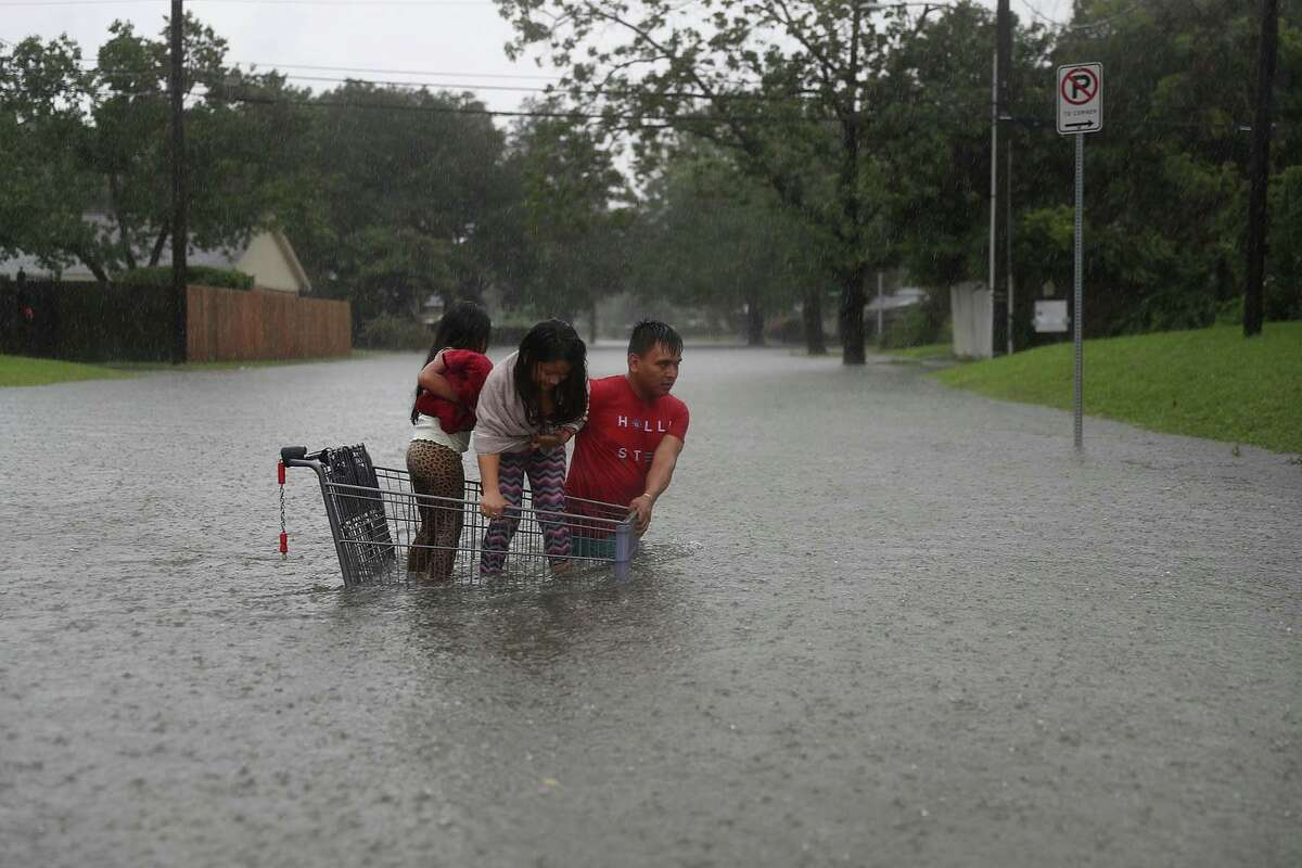 HOUSTON, TX - AUGUST 27: A man helps children across a flooded street as they evacuate their home after the area was inundated with flooding from Hurricane Harvey on August 27, 2017 in Houston, Texas. Harvey, which made landfall north of Corpus Christi late Friday evening, is expected to dump upwards to 40 inches of rain in Texas over the next couple of days. (Photo by Joe Raedle/Getty Images)