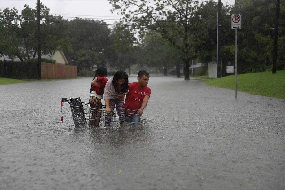 HOUSTON, TX - AUGUST 27: A man helps children across a flooded street as they evacuate their home after the area was inundated with flooding from Hurricane Harvey on August 27, 2017 in Houston, Texas. Harvey, which made landfall north of Corpus Christi late Friday evening, is expected to dump upwards to 40 inches of rain in Texas over the next couple of days.  (Photo by Joe Raedle/Getty Images) Photo: Joe Raedle/Getty Images
