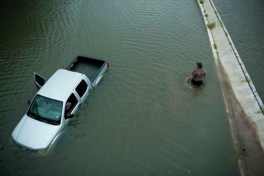 A truck driver walks past an abandoned truck while checking the depth of an underpass during the aftermath of Hurricane Harvey on August 28, 2017 in Houston. Photo: BRENDAN SMIALOWSKI/AFP/Getty Images