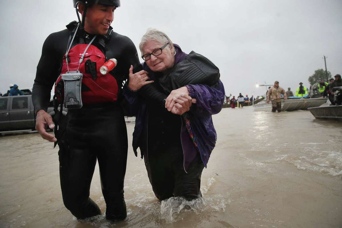 HOUSTON, TX - AUGUST 28: Barb Davis, 74. is helped to dry land after being rescued from her flooded neighborhood after it was inundated with rain water, remnants of Hurricane Harvey, on August 28, 2017 in Houston, Texas. Harvey, which made landfall north of Corpus Christi late Friday evening, is expected to dump upwards to 40 inches of rain in areas of Texas over the next couple of days. (Photo by Scott Olson/Getty Images)