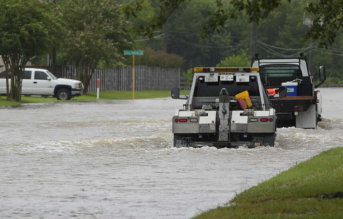 Trucks make their way through floodwaters in Cypress, Texas on August 29, 2017. / AFP PHOTO / MANDEL NGAN (Photo credit should read MANDEL NGAN/AFP/Getty Images)