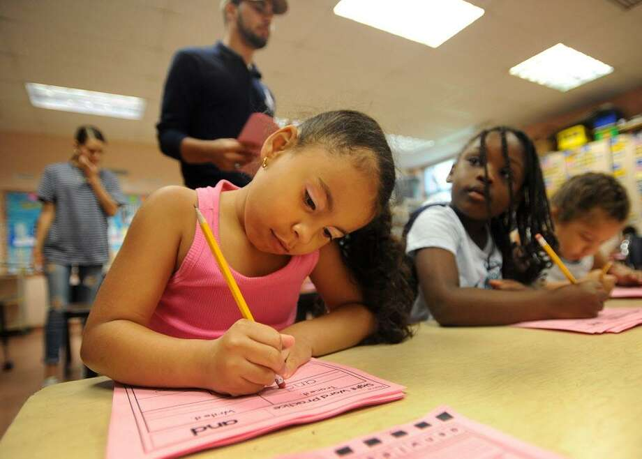 First graders Maliyah Baez, left, and Dinneen Fearon, both 6, get down to work during the first day of the Lighthouse summer program at Luis Munoz Marin School in Bridgeport, Conn. on Wednesday, July 5, 2017. The city Board of Education narrowly approved the program, a fixture in city schools since it's founding in 1993. Photo: Brian A. Pounds / Hearst Connecticut Media / Connecticut Post