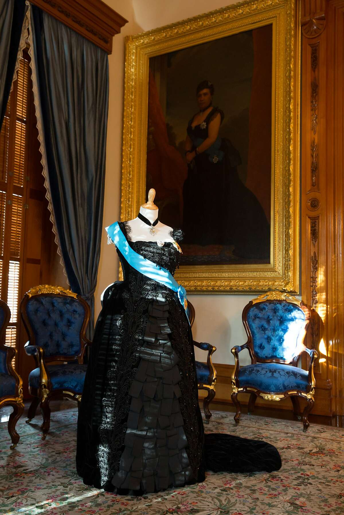 Queen Liliuokalani�s ribbon dress, one of a series of reproduced royal gowns, is seen in Iolani Palace�s Blue Room, below a portrait of her wearing the original.
